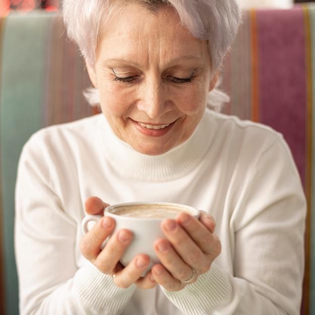Vue de face senior femme tenant une tasse de café Photo gratuit