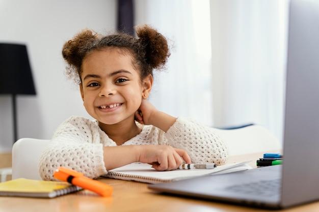 Vue De Face De Smiley Petite Fille à La Maison Pendant L'école En Ligne Avec Ordinateur Portable Photo gratuit