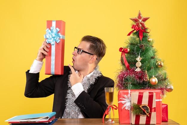 Vue De Face Travailleur Masculin Assis Avec Des Cadeaux De Noël Photo gratuit