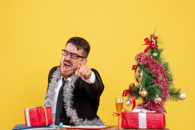 Vue De Face Travailleur Masculin Assis Et Célébrant Noël Au Travail Crier Sur Jaune Photo gratuit