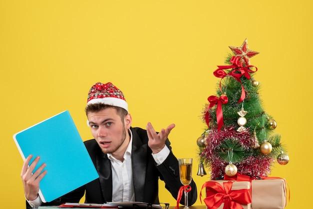 Vue De Face Travailleur Masculin Tenant Des Documents Autour De Petit Arbre De Noël Et Présente Sur Jaune Photo gratuit