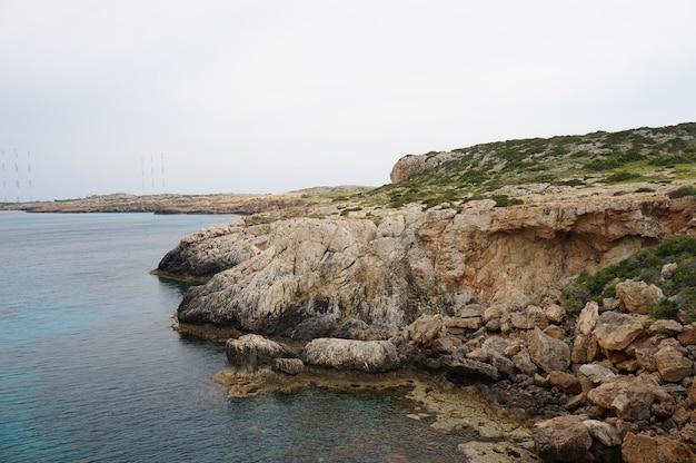 Vue Fascinante Sur La Côte D'un Océan Avec Des Montagnes Rocheuses Sous Le Ciel Bleu Photo gratuit