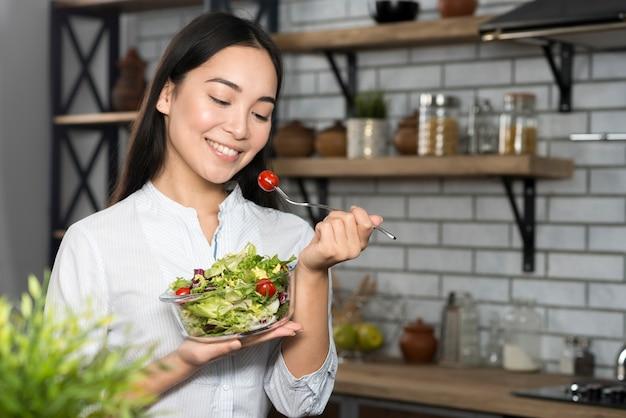 Vue frontale, de, femme mange, tomate cerise, à, légumes verts Photo gratuit