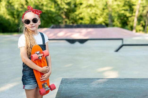 Vue frontale, de, fille, à, skateboard orange Photo gratuit