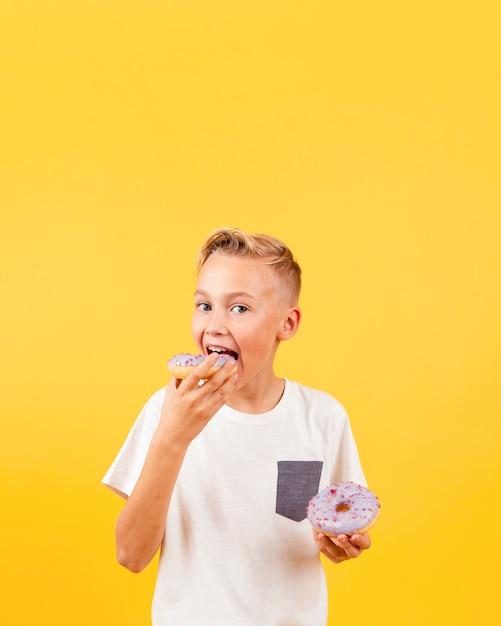 Vue frontale, garçon, manger, beignets Photo gratuit