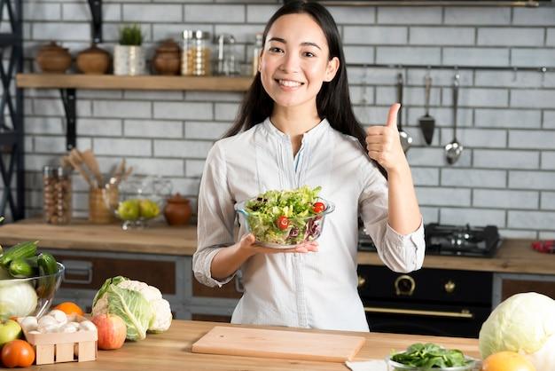Vue frontale, de, heureux, jeune femme, tenant verre, de, bol, à, salade, montrer pouce, signe haut, dans, cuisine Photo gratuit