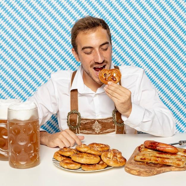 Vue frontale, de, homme mange, bretzels allemands Photo gratuit