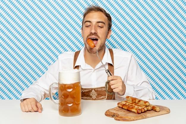Vue frontale, de, homme mange, saucisses, à, bière Photo gratuit