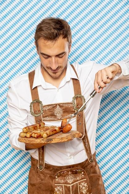 Vue frontale, de, homme, à, plaque, de, saucisses allemandes Photo gratuit