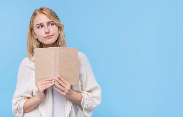 Vue frontale, jeune femme, tenue livre Photo gratuit