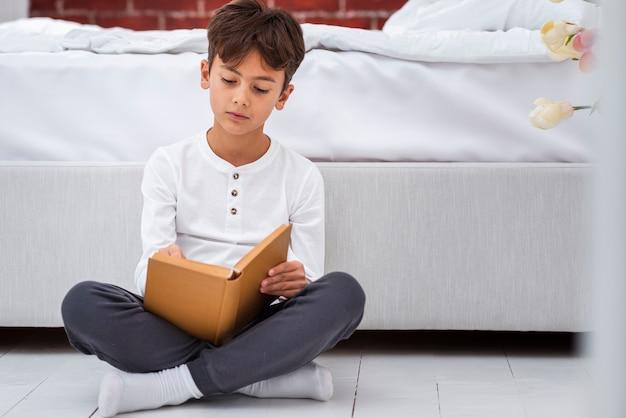 Vue frontale, jeune garçon, chez soi, lecture Photo gratuit