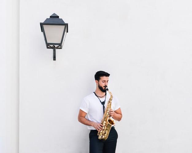 Vue frontale d'un musicien jouant du saxophone Photo gratuit