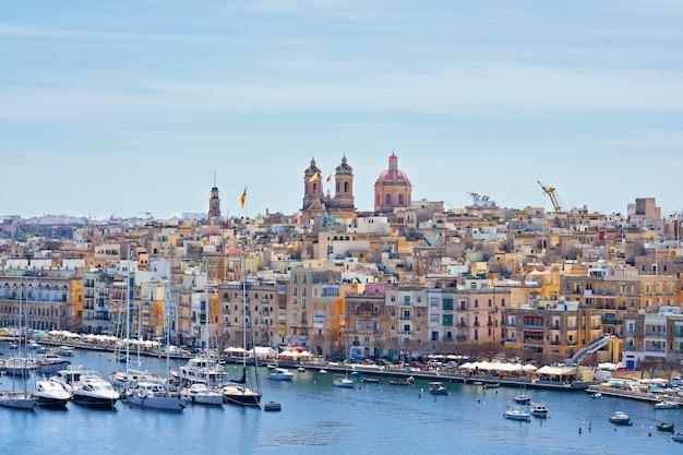 Vue générale sur le front de mer et la ligne d'horizon de la ville de birgu dans la baie avec des bateaux colorés à malte. Photo Premium