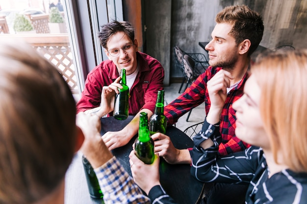 Vue grand angle d'amis assis ensemble en appréciant la bière Photo gratuit