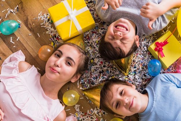 Vue Grand Angle D'amis Couchés Sur Un Plancher En Bois Entourés D'un Cadeau; Ballon Et Confettis Photo gratuit