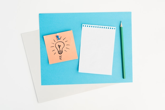 Vue grand angle d'ampoule dessiné sur pense-bête attaché avec une punaise sur fond blanc Photo gratuit