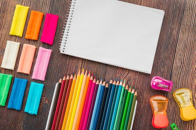 Vue grand angle d'argile coloré et un crayon avec le bloc-notes en spirale blanche Photo gratuit
