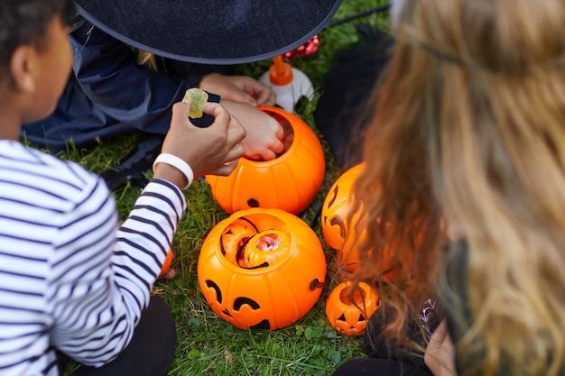 Vue Grand Angle Au Groupe D'enfants Portant Des Costumes Prenant Des Bonbons De Seaux D'halloween à L'extérieur, Copiez L'espace Photo Premium