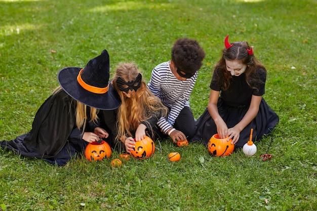 Vue Grand Angle Au Groupe Multiethnique D'enfants Portant Des Costumes Prenant Des Bonbons De Seaux D'halloween à L'extérieur, Copiez L'espace Photo Premium