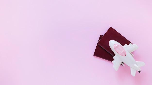 Vue grand angle de l'avion et du passeport sur une surface rose Photo gratuit