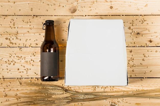 Vue grand angle de la boîte en carton; bouteille de bière et épis de blé sur une planche en bois Photo gratuit