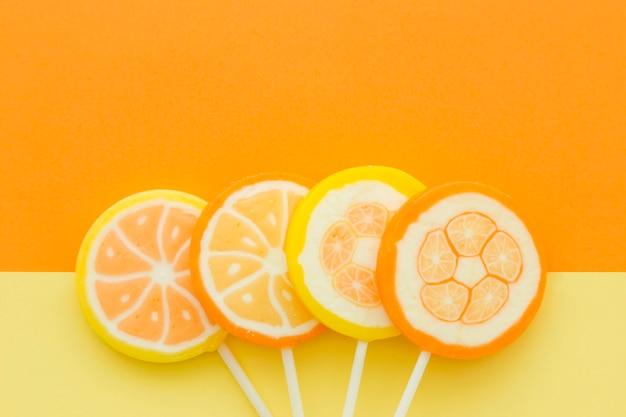 Vue grand angle de bonbons aux agrumes sur fond jaune et orange Photo gratuit