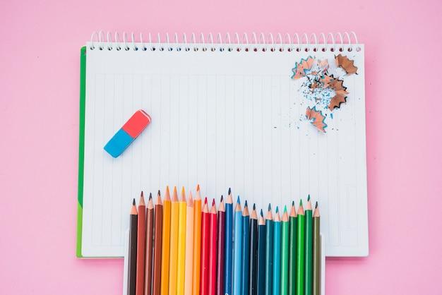Vue grand angle des couleurs de crayon avec une gomme et un crayon à raser sur un cahier à spirale Photo gratuit