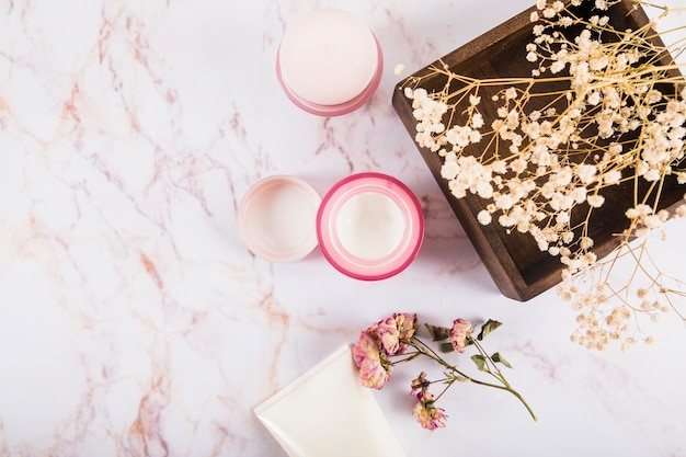 Vue grand angle de crème nourrissante et de fleurs sur marbre Photo gratuit