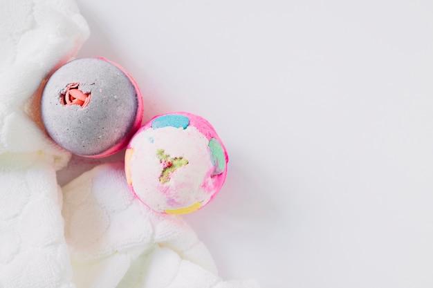 Vue grand angle de deux bombes de bain et serviette sur une surface blanche Photo gratuit