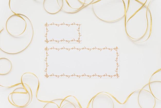 Vue grand angle de deux cartes vierges entourées de rubans sur une surface blanche Photo gratuit