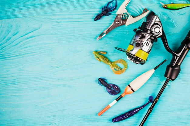 Vue grand angle de divers équipements de pêche sur fond turquoise Photo gratuit
