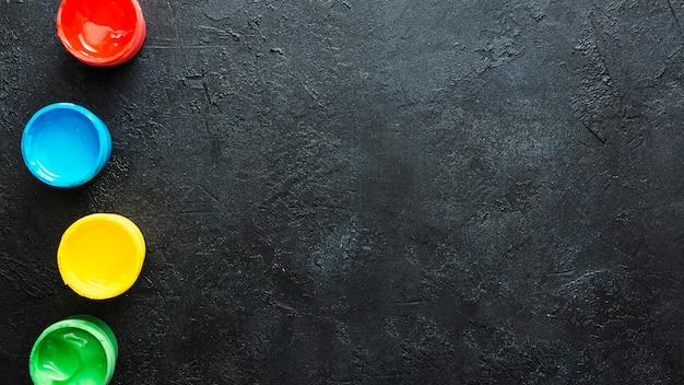 Vue grand angle du conteneur de peinture couleur eau sur fond noir Photo gratuit