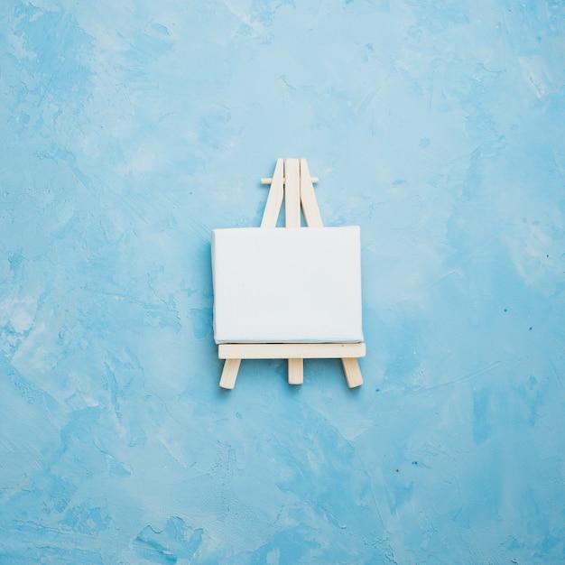 Vue grand angle du petit chevalet miniature sur bleu texturé rugueux Photo gratuit