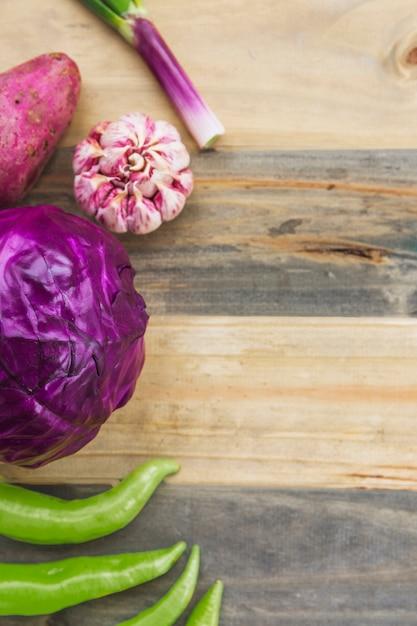 Vue grand angle du piment vert; chou rouge; ail et patate douce sur une planche en bois Photo gratuit