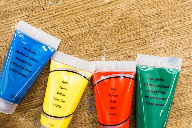 Vue grand angle du tube de couleurs liquides sur une surface en bois Photo gratuit