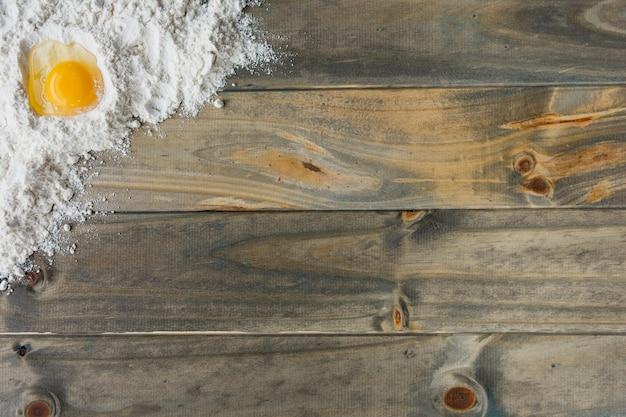 Vue grand angle de farine et d'oeuf sur fond en bois Photo gratuit