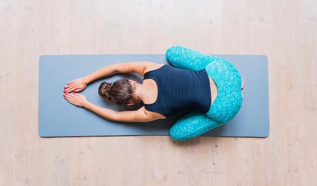 Vue Grand Angle D'une Femme Faisant Des Exercices Sur Un Tapis De Yoga Photo gratuit