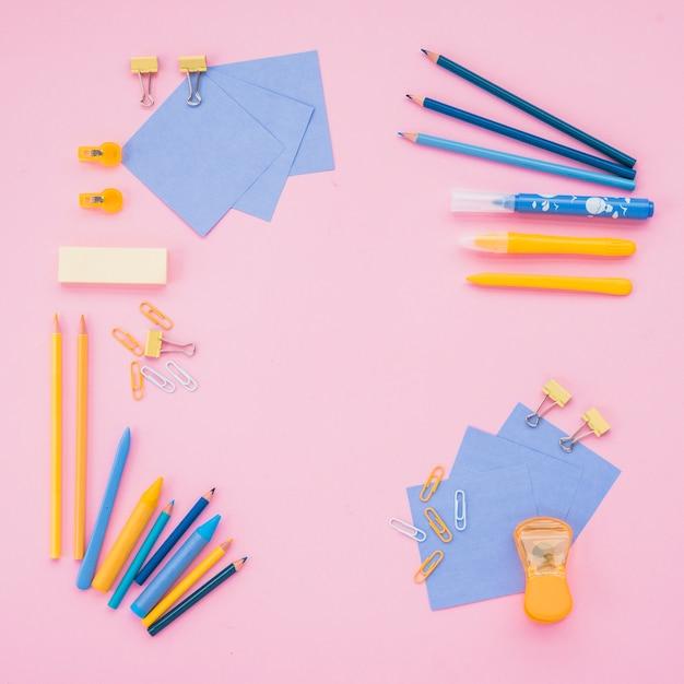Vue grand angle de fournitures scolaires sur papier peint rose Photo gratuit