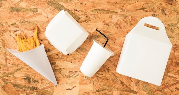 Vue grand angle des frites; coupe et emballages sur une surface en bois Photo gratuit