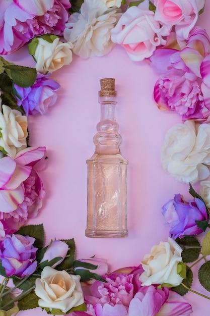 Vue grand angle d'huile essentielle entourée de fleurs fraîches sur fond rose Photo gratuit