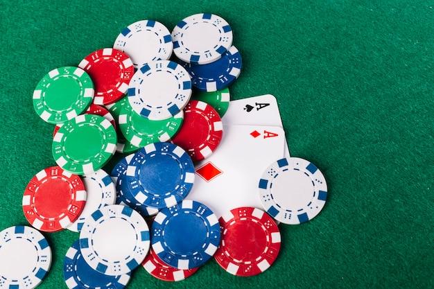 Vue grand angle de jetons de poker multicolores et de deux cartes à jouer sur une surface verte Photo gratuit