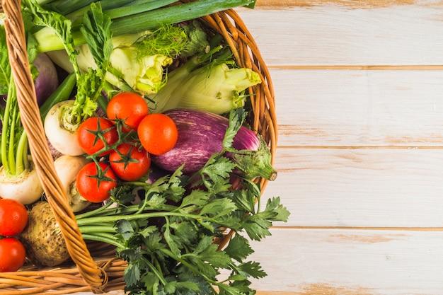 Vue grand angle de légumes biologiques frais dans un panier en osier sur une surface en bois Photo gratuit