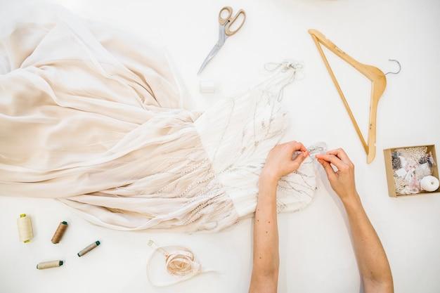 Vue grand angle de la main d'un créateur de mode travaillant sur la robe sur fond blanc Photo gratuit