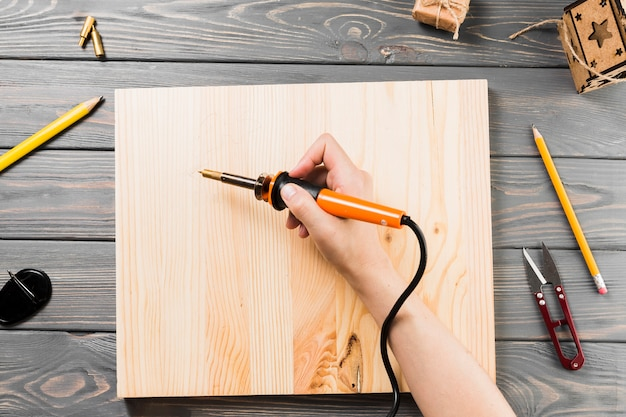 Vue grand angle de la main tenant la machine à souder sur une planche de bois pour couper la forme Photo gratuit