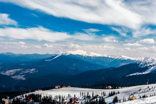 Vue grand angle de maisons sur le paysage de montagne enneigée Photo gratuit