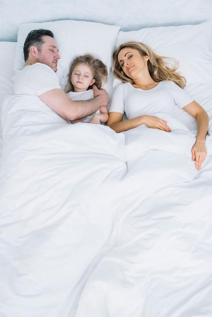 Vue grand angle de la mère; fille et père reposant sur un lit blanc Photo gratuit