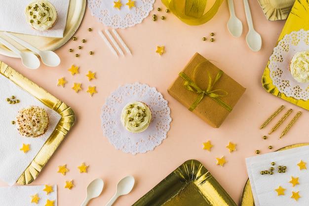 Vue grand angle de muffins et cadeaux sur fond coloré décoratif Photo gratuit