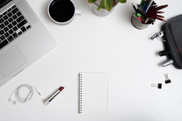 Vue grand angle de l'ordinateur portable; tasse à café; trousse de maquillage et crayons sur le bureau Photo gratuit