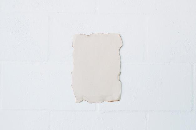 Vue grand angle de papier brûlé sur un mur blanc Photo gratuit