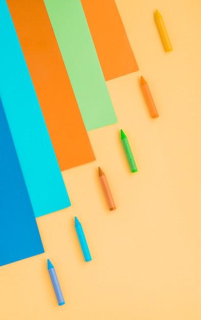 Vue grand angle de papier multicolore et de cire de crayon de couleur Photo gratuit